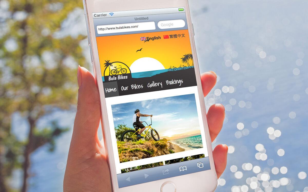 Lady holding mobile phone with Bula Bikes Fiji website